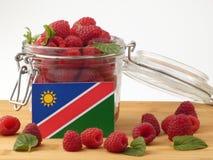 Namibijska flaga na drewnianym panelu z malinkami odizolowywać na w Obraz Stock