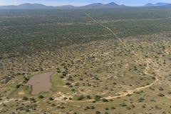 Namibische Landschaft der Vogelperspektive mit waterhole, weiten Wegen und ACA Lizenzfreies Stockfoto