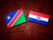 Namibisk flagga med den kroatiska flaggan på en isolerad trädstubbe Fotografering för Bildbyråer