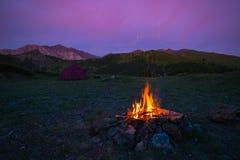 Namiotu i palenia obóz podpala przy półmrokiem na górach Lato eksploracja w Alps i przygody Selekcyjna ostrość na ogieniu, kolor zdjęcie royalty free