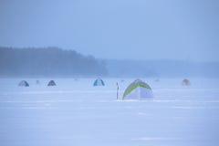 Namioty na śnieżystym polu blisko lasu Fotografia Royalty Free