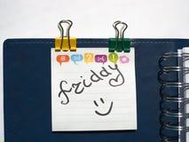 Namnet av dagen av den skriftliga veckan på ett klibbigt ark i en blå anteckningsbok med vårar arkivfoto