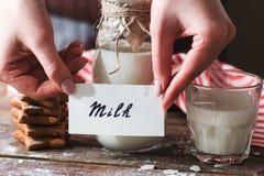 Namnge flaskan av mjölka med kakacloseupen royaltyfria bilder