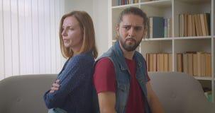 Namorada e namorado em briga sentada de volta ao sofá pensando sobre o conflito vídeos de arquivo