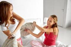 Namoradas adolescentes felizes que lutam descansos em casa foto de stock