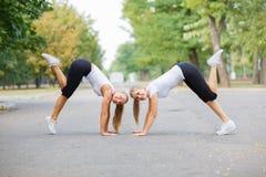 Namoradas energéticas em um treinamento da aptidão em um fundo do parque Conceito do esporte e dos estiramentos Copie o espaço Fotografia de Stock Royalty Free