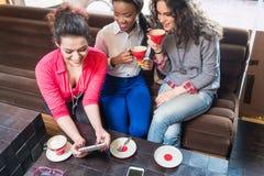 Namoradas que sentam-se junto no café e que mostram fotos em smar Imagens de Stock Royalty Free