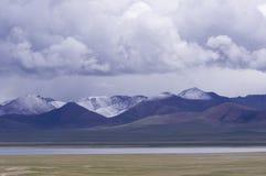 Namtso Jezioro i śniegu góra pod chmurą zdjęcie stock