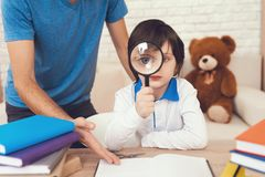 Nan spends time with son. Father is engaged in raising child. Father helps his son to do homework. A men spends time with his son. The father of boy is engaged stock image