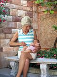 Nana. Senior woman sitting outside with her great granddaughter on her lap Stock Image