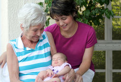 Nana's Pride. Elderly lady admiring her grand daughters baby Royalty Free Stock Photos