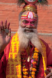 Sadhu man waves a blessing over crowd-. NAND BAGH, INDIA - NOVEMBER 24, 2010-Sacred holy man, Sadu, with brightly painted face and clothing, blesses travelers on Royalty Free Stock Images