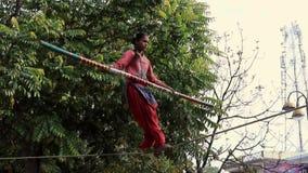 Nandgeon, India - 20180225 - Girl Crosses Slackroap to Entertain Passing Crowd stock video footage