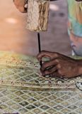 Nang Yai, Shadow Play, The hands of the craftsmen carved Leather with wooden hammer peg product, small village crafts. royalty free stock photography