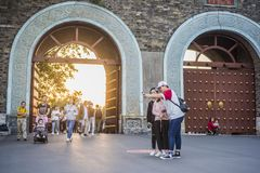 Young people taking photos with mobile phone in front of the ancient city gate at sunset time royalty free stock images