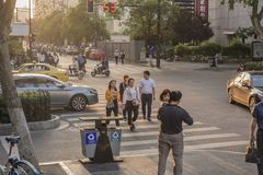 Sunset city scenery, pedestrians, traffic flow. Royalty Free Stock Photography
