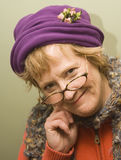 Nanny. Beauitful older woman with a fun expression wearing a purple hat and red sweater Royalty Free Stock Images