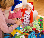 Nanny helping  daughters  to make decoration for Xmas Royalty Free Stock Image
