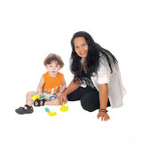 Nanny plays with little boy. A Filipino nanny sitting on the floor playing with a little three year old Royalty Free Stock Photos