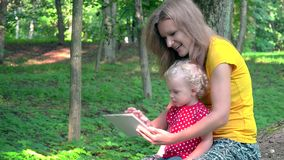Nanny woman with cute baby girl using tablet computer in park. stock video