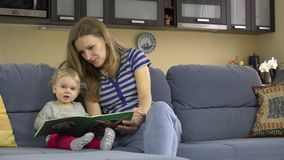 Nanny woman story telling read book for child at kindergarten at work. stock footage