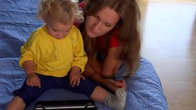 Nanny woman teaching little toddler girl using tablet pc sitting on bed. stock video