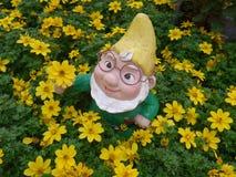 Nano del giardino con la carriola e lumaca su un letto di fiore Fotografie Stock Libere da Diritti