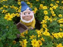 Nano divertente del giardino con la carriola in un letto di fiore Fotografia Stock