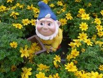 Nano divertente del giardino con la carriola in un letto di fiore Fotografia Stock Libera da Diritti