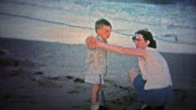 nantucket 美国- 1957年:孩子在海滩第一次看见海浪,当安全地,得到惊吓时 股票视频