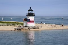 Nantucket Island Lighthouse with American Flag on Quiet Summer D. Brant Point lighthouse on Nantucket Island has an American flag wrapped arount the tower royalty free stock photography