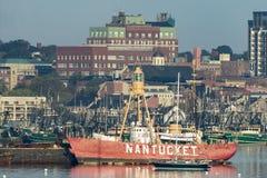 Nantucket Lightship temporary tie up. New Bedford, Massachusetts, USA - October 19, 2017: Obsolete Nantucket Lightship temporarily tied up against barge in busy Stock Image