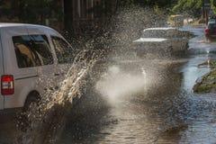 Napędowi samochody na zalewającej drodze podczas powodzi powodować podeszczowymi burzami Samochodu pławik na wodzie, zalewa ulicy obrazy stock