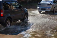 Napędowi samochody na zalewającej drodze podczas powodzi powodować podeszczowymi burzami Samochodu pławik na wodzie, zalewa ulicy zdjęcia stock