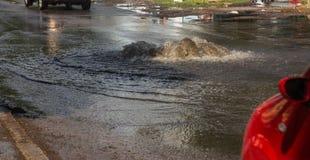 Napędowi samochody na zalewającej drodze podczas powodzi powodować podeszczowymi burzami Samochodu pławik na wodzie, zalewa ulicy zdjęcie stock