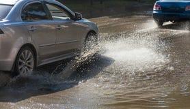Napędowi samochody na zalewającej drodze podczas powodzi powodować podeszczowymi burzami Samochodu pławik na wodzie, zalewa ulicy fotografia stock