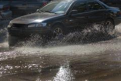 Napędowi samochody na zalewającej drodze podczas powodzi powodować podeszczowymi burzami Samochodu pławik na wodzie, zalewa ulicy zdjęcia royalty free