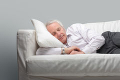 Nap. Portrait of a senior man lying in a couch and relaxing Royalty Free Stock Image