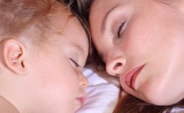 Nap. Face of baby and mother sleeping Stock Photography