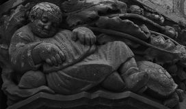 The nap. Shot in black and white. Placed on the facade of this historic building, sculpture on the capital representing a male figure sleeping. Set in Sitges Stock Images