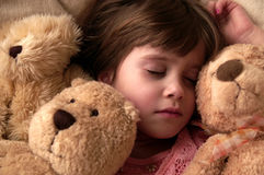 Nap time. A young girl taking a nap with her teddy bears stock photo
