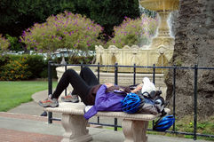 Nap Time. Cyclist taking a rest on park bench Stock Image