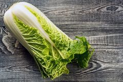 Napa or Chinese cabbage on wooden background. Napa or Chinese cabbage on rustic black wooden background royalty free stock image