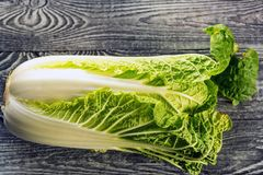 Napa or Chinese cabbage on wooden background. Napa or Chinese cabbage on rustic black wooden background stock image