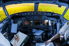 Napa Valley cockpit. Airplane cockpit flying on Napa Valley at sunset, California, United States, with pilots arms and blank white papers for copy space royalty free stock photos