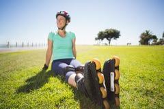 Napad dojrzała kobieta w rolkowych ostrzach na trawie Fotografia Stock