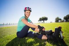 Napad dojrzała kobieta wiąże jej rolkowych ostrza na trawie Fotografia Royalty Free