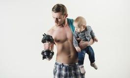Napad i energiczny Ojciec i dziecko trenuje wpólnie Silny mężczyzna z dumbbells chwyta chłopiec Ojciec budowy bicepsy obraz royalty free