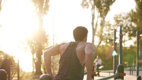 Napad, mięśniowy mężczyzna w koszula przychodził lokalna sport ziemia i zaczynać trenować na horyzontalnym przecinającym barze Rz zdjęcie wideo
