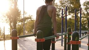 Napad, mięśniowy mężczyzna w koszula przychodził lokalna sport ziemia i zaczynać trenować na horyzontalnym przecinającym barze tr zbiory wideo